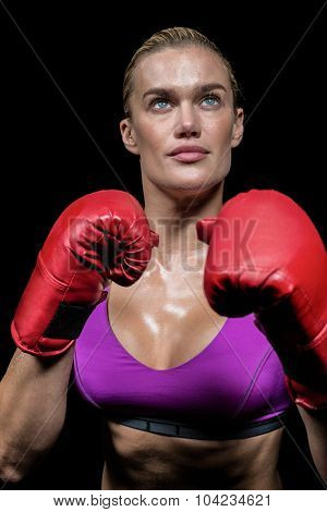 Confident female boxer with gloves looking up against black background