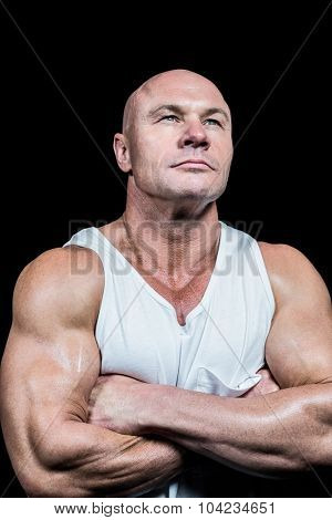 Confident bodybuilder with arms crossed against black background