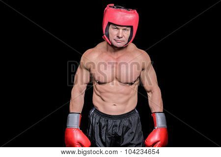 Portrait of shirtless man with boxing headgear and gloves against black background