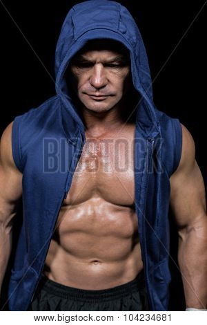 Muscular man in blue hood against black background