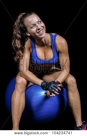 Cheerful fit woman sitting on exercise ball against black background