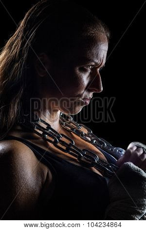 Side view of female angry athlete holding chain against black background