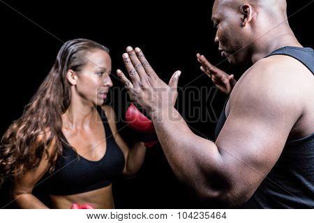 Trainer instructing female boxer against black background