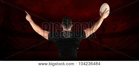 Rugby player celebrating with the ball against rugby stadium