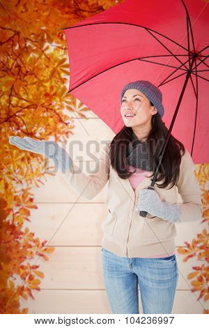 Smiling brunette feeling the rain against autumn leaves pattern