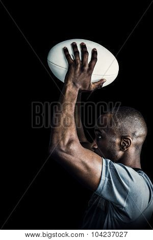 Rugby player throwing ball against black