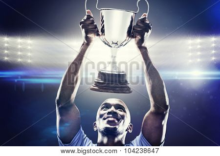 Happy sportsman looking up while holding trophy against spotlights