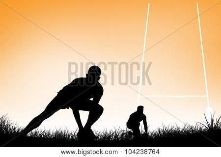 Rugby player getting ready to kick ball against orange vignette