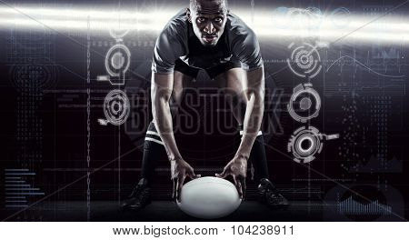 Sportsman holding ball while playing rugby against spotlights
