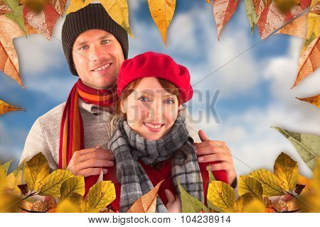 Couple smiling at the camera against blue sky with white clouds