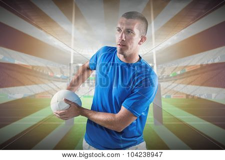 Rugby player looking away while holding ball against linear design
