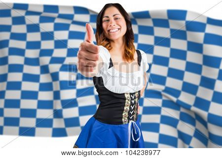 Pretty oktoberfest girl showing thumbs up against blue and white flag