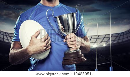 Rugby player holding trophy and ball against rugby stadium