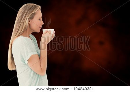 Pretty blonde standing and holding hot beverage against dark background