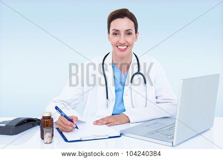 Portrait of smiling female doctor writing on pad against blue vignette background