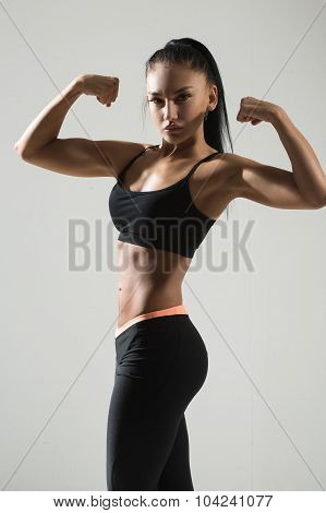 Portrait of young fitness woman shows biceps.