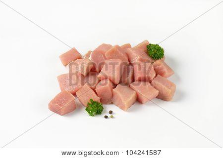 heap of diced raw pork tenderloin on white background