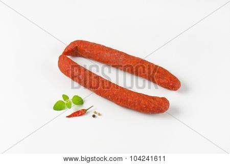 pair of pepperoni sausages on white background