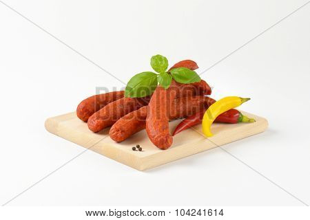 four pepperoni sausages on wooden cutting board