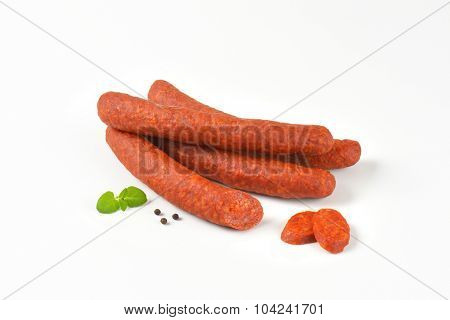 whole and sliced pepperoni sausages on white background