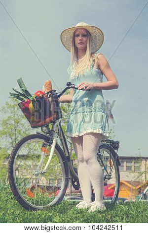 Attractive blonde woman with straw hat posing next to bike with basket  full of groceries. Post processed with vintage filter.