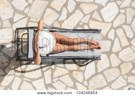 WOman relaxing on a sun bed by the swimming pool