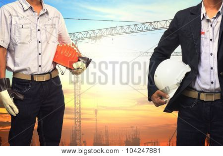 Two Engineer Man Working With White Safety Helmet Against Crane And  Building Construction Site Use