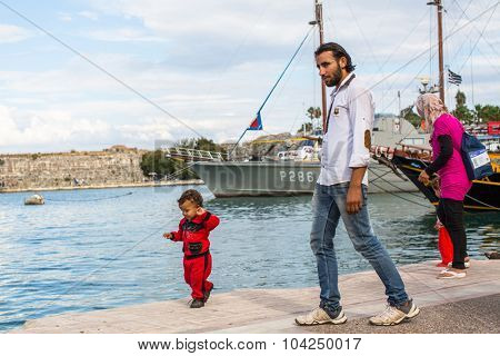KOS, GREECE - SEP 27, 2015: Unidentified Syrian refugees on a beach. Kos island is located just 4 km from the Turkish coast and refugees come from Turkey in an boat.