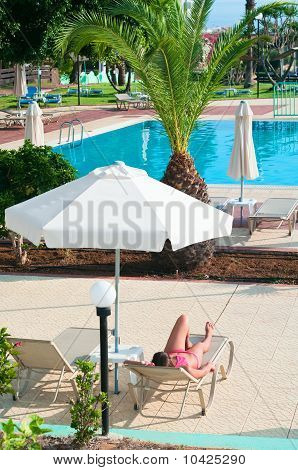 A Beautiful Young Girl In A Bikini Sunbathing On A Lounger Near The Hotel Swimming Pool Under Paraso