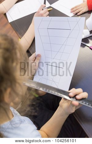 Girl with a sheet of paper and a ruler in hands making crafts
