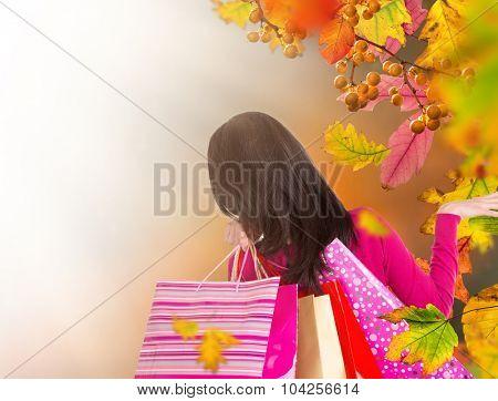 Beautiful woman holding shopping bags, buying in autumn season.