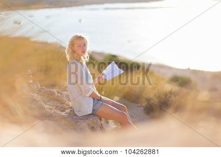 Woman enjoys reading on beautiful sandy beach.