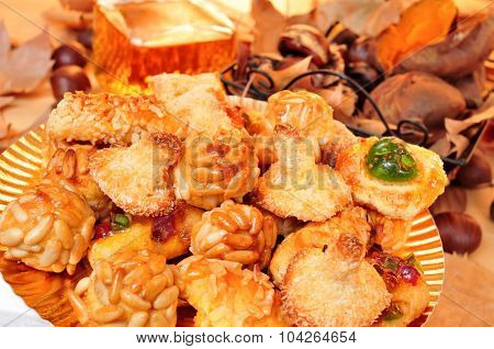 closeup of a plate with panellets, some roasted chestnuts and sweet potatoes in a basket, and sweet wine in a glass bottle, typical snack in All Saints Day in Catalonia, Spain