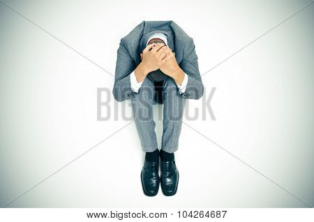 a businessman curled up in the floor with his head between his knees and his hands in his head, slight vignette added