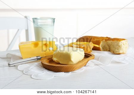 Fresh bread with cheese and butter on table in kitchen