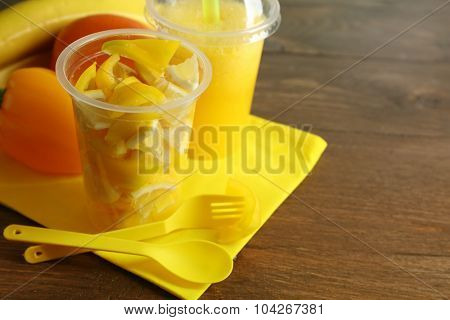 Yellow vegetable and fruit salad and healthy fresh drink in plastic cups on wooden background. Colorful diet concept