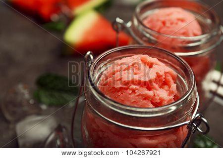 Watermelon ice cream in glass jars on dark background