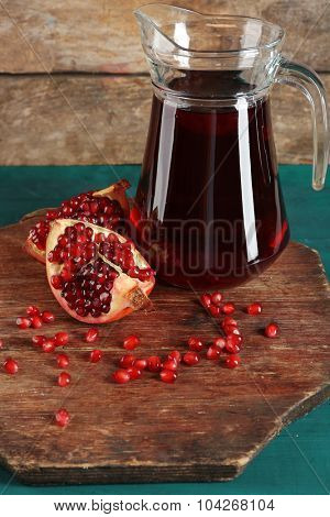 Pomegranate and glass jug of fresh juice on wooden table, closeup