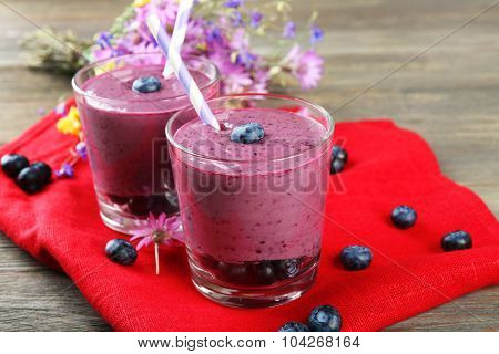 Glasses of blueberry smoothie on red napkin, closeup