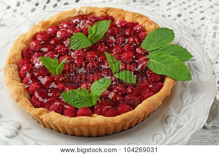 Tart with raspberries, on wooden background