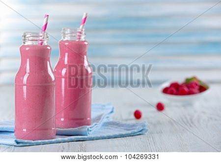 Bottles of raspberry milk shake with berries on wooden table close up