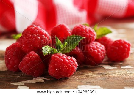 Fresh red raspberries on rustic wooden table, closeup