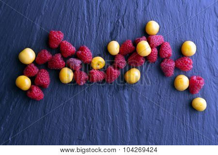 Ripe raspberries with cherry-plums on wooden table close up