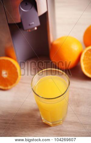 Juicer and orange juice on kitchen table