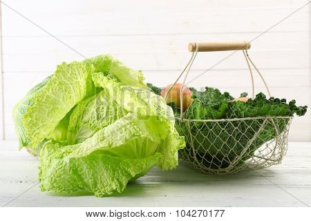 Savoy cabbage and other vegetables on wooden background