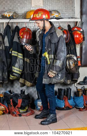 Full length of firefighter looking at walkie talkie against uniforms hanging in fire station