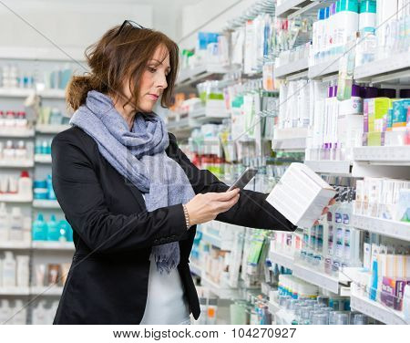 Mid adult female customer scanning product through mobile phone in pharmacy