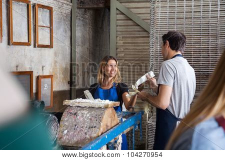 Man giving paper strips to female colleague in factory