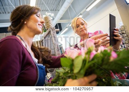 Female customer showing something on digital tablet to florist in flower shop