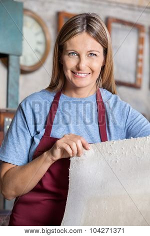 Portrait of confident female worker holding paper sheet in factory